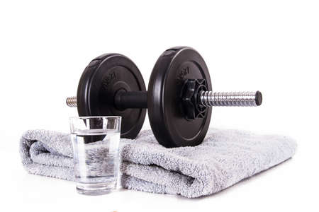 Black gym barbell, dumbbell with disks, blue towel and glass of water, isolated on white background. Stock Photo