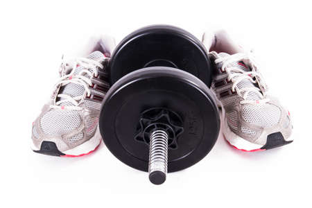 Black gym barbell, dumbbell with disks and sport shoes, isolated on white background. photo