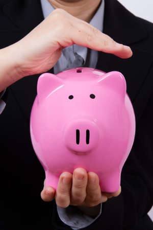 Business woman holding and covering pink piggy bank. photo