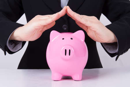 Business woman, roof shaped hands for estate, pink piggy bank. photo