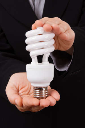 economical: Business woman shows and holds economical lightbulb.