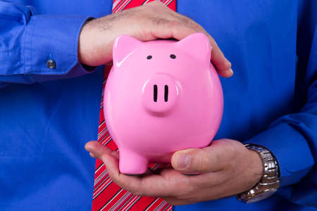 Businessman with blue shirt covering and protecting pink piggy bank with his hands. photo