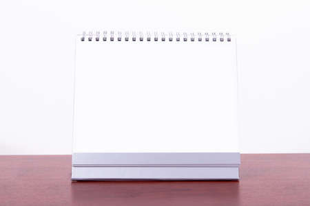 Single blank desk calendar on wooden table, isolated on white background. photo