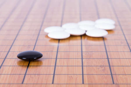 battle plan: Black stone standing out from white pieces on Chinese go game board.