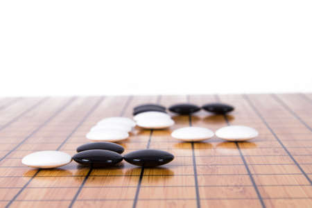 battle plan: White stone standing out from black pieces on Chinese go game board, isolated on white background. Stock Photo