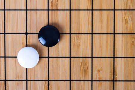 Close up view of black and white stone pieces on Chinese go game board.