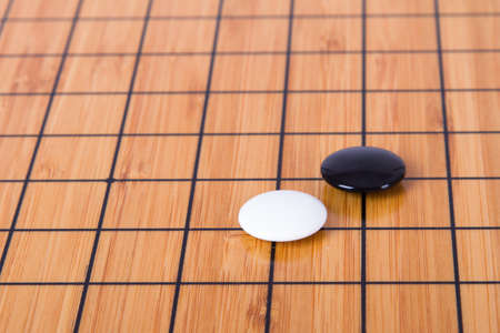 battle plan: Close up view of black and white stone pieces on Chinese go game board.