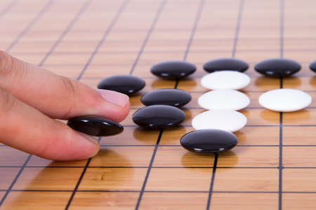 battle plan: Close up view of hand playing black and white stone pieces on Chinese go game board.