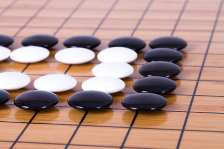 battle plan: Black and white figures on squares, Chinese go game on board. Stock Photo