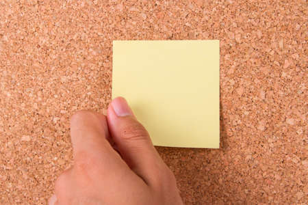 Hand and blank, blue sticky post it note for your message on cork bulletin board. Stock Photo - 22621784