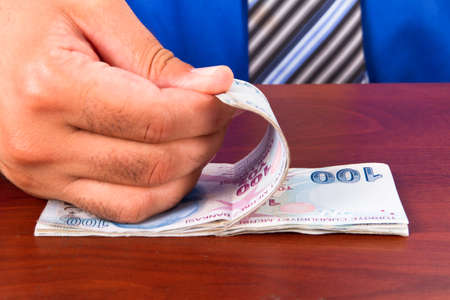 tl: Businessman hand countaing one hundred Turkish lira banknotes on wooden t able. Stock Photo
