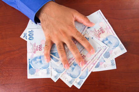 tl: Hand on stack of one hundred Turkish lira banknotes on wooden table.