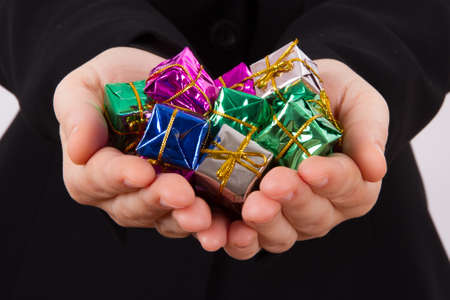 Hands extend colorful gift boxes. photo
