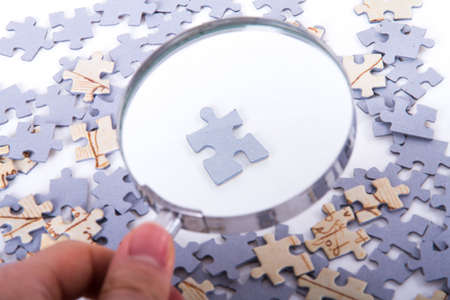 Hand holding classic style magnifying glass and examining single little puzzle piece among others on white. Stock Photo