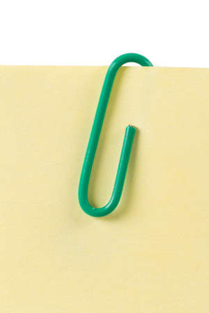 Top view of yellow sticky post it note with green paper clip, isolated on white background. photo