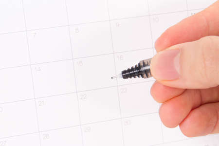 Desk or event calendar and hand holding pen which is pointing a day. Stock Photo - 22623981
