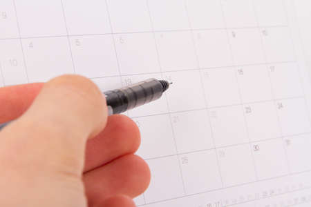 Desk or event calendar and hand holding pen which is pointing a day. photo