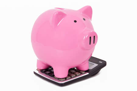 Pink piggy bank on calculator, isolated on white background. photo