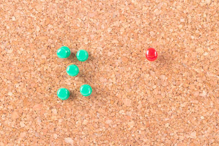 distinction: Red push pin standing out on cork bulletin board.