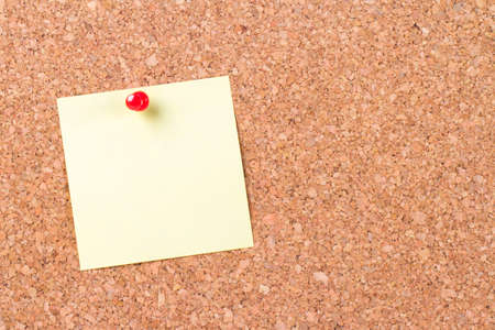 cork board: Blank, empty, yellow sticky post it pinned on cork bulletin board with red pin, ready for your message. Stock Photo