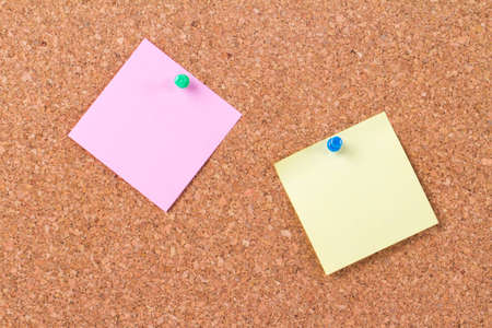 Blank, empty, pink and yellow sticky post it notes on cork bulletin board. photo