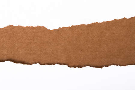 Teared, ripped paper on brown background photo