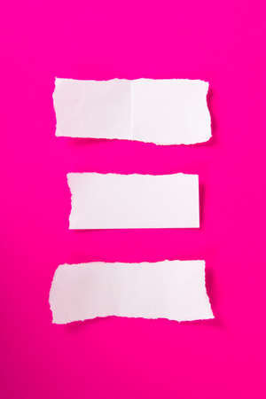 Collection of white torn pieces of paper on pink background, ready for your messages. photo