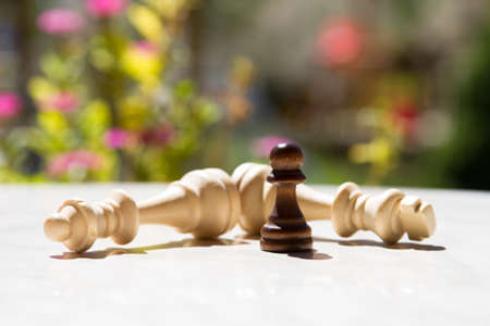 battle plan: Chess pieces, pawn and queens on white table with blurry background.
