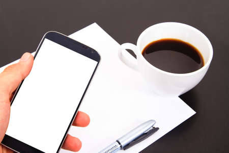 Hand showing smart phone with white, blank screen and paper, pen, coffee cup on wooden table. Stock Photo - 22683673