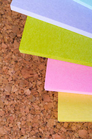 Multi colored sticky post it notes on cork bulletin board. photo