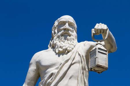 Philosopher Diogenes holding light sculpture on blue sky, Sinop, Turkey