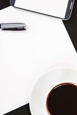 Smart phone with blank, white screen, ceramic coffee cup, pen and empty paper, top view on wooden table. Stock Photo - 22684309