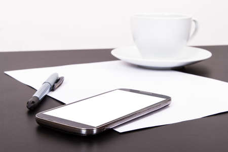 Smart phone with blank, white screen, ceramic coffee cup, pen and empty paper on wooden table, isolated on white background. Stock Photo - 22684314