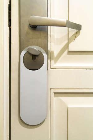 Door handle on old wooden door with hanging sign in hotel room. Stock Photo - 22721151