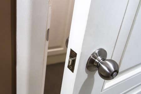 Handle on white opened wooden door. photo