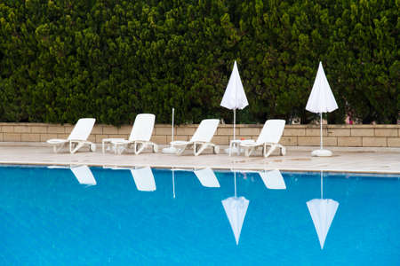 Sunbeds and umbrellas near blue clear swimming pool. Stock Photo