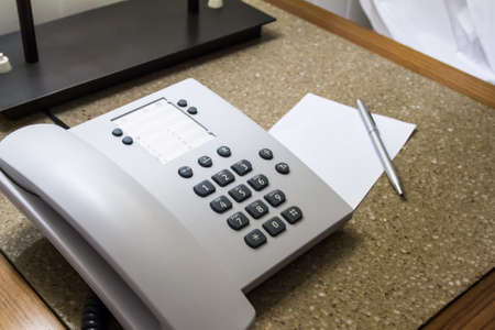 Telephone for customer service and blank white note paper with pen in hotel room. photo