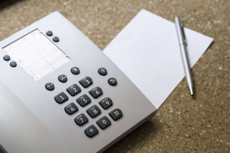 dial pad: Telephone for customer service and blank white note paper with pen in hotel room.