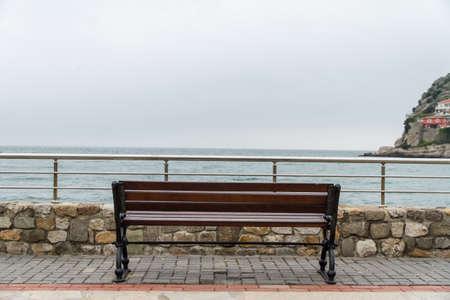 pesantezza: Panca di legno vuoto con il punto di vista che guarda al mare, tempo nuvoloso.