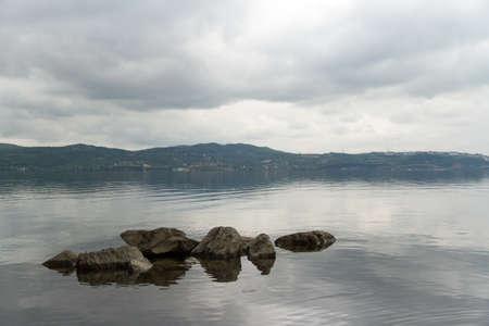 pesantezza: Lago e cielo nuvoloso con pietre.