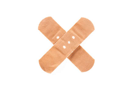 Adhesive bandage, plaster as cross sign, isolated on white background. photo