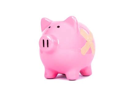band aid: Adhesive bandage, plaster on pink piggy bank, isolated on white background. Stock Photo
