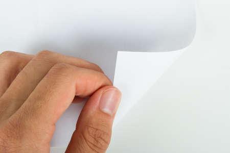 Hand turning blank page, isolated on white background. Stock Photo