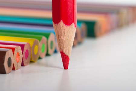 Colorful pencils, focused on red pencil, isolated on white background.