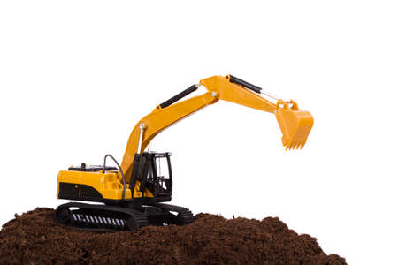 Construction machine, excavator on pile of soil, isolated on white background. photo