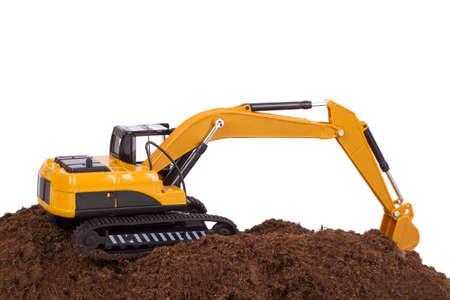 Construction machine, excavator on pile of soil digging a trench, isolated on white background. photo