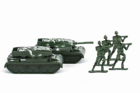 attacker: Miniature toy tank and attacker soldiers, isolated on white background. Stock Photo