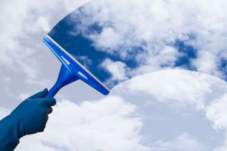 Hand in gloves holding squeegee and cleaning the blue sky.