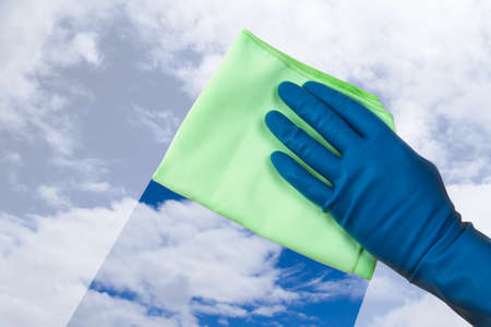 Hand in gloves holding green rag and cleaning the blue sky. photo