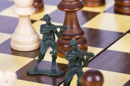 battle plan: Close up view of miniature toy soldiers on chess board.